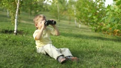 Little boy with binoculars sitting on the grass. Thumbs up. Ok. Stock Footage