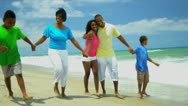 African American family enjoying summer vacation walking together on beach   Stock Footage