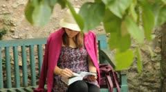 Girl sitting reading in Versailles garden (HD) k Stock Footage