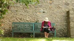 Teenage girl reading book on bench in Versailles garden (HD) k Stock Footage