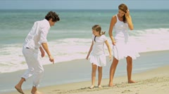 Attractive Caucasian family playing together dressed in white on beach   - stock footage