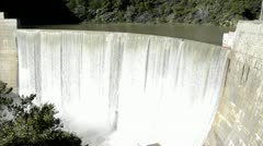 Tilt down shot of Matilija Creek spilling over the obsolete Matilija Dam after a Stock Footage