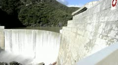 Dolly shot of Matilija Creek spilling over the obsolete Matilija Dam after a - stock footage