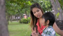 Asian mother and son talking while in a park - dolly shot - stock footage