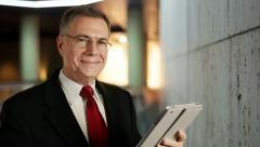 Businessman using a tablet smiles at camera Stock Footage