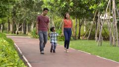 Young happy Asian family walking in the park together Stock Footage