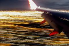 Lentokone lentää Streaked City Lights Kuvituskuvat