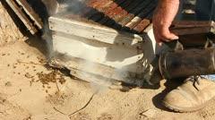 Beekeeper fumigates a beehive. - stock footage