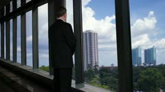 Businessman looking out of his office window smiles at camera - stock footage