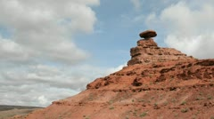 Storm clouds pass over a small rock tower in Mexican Hat Canyon. Stock Footage