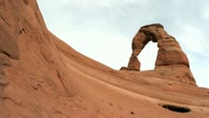 Delicate Arch in Utah's Arches National Park crowns the crest of a red rock Stock Footage