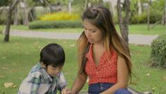 asian mother and son reading together in a park - tracking shot - stock footage