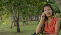 Young Asian woman talking on her cell phone - dolly reveal Stock Footage