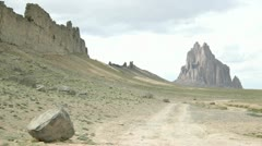 A dirt road leads to Shiprock monument. - stock footage