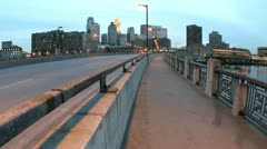 Pedestrians and vehicles cross a bridge in downtown Minneapolis as the evening Stock Footage