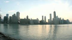 Lake Michigan reflects the Chicago skyline as evening darkens into a colorful Stock Footage