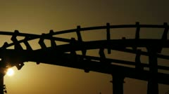 Line of dragon roller coaster rail (silhouette at sunset) Stock Footage