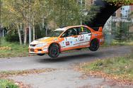 Stock Photo of Orange rally Mitsubishi going in for a jump