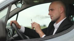 Young businessman smoking cigarettes in car - stock footage