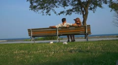 Couple Relaxing On Beach Bench Stock Footage
