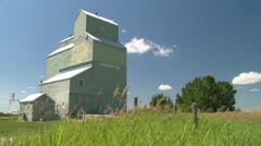 Grain elevator Herronton, with blowing grass in fg, wide shot Stock Footage