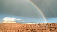 A rainbow glows in the sunlight as it arches over Goblin Valley State Park. - stock footage