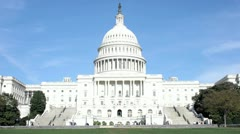 Workers and pedestrians enter, exit, and walk by the United States Capitol Stock Footage