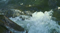 Sunlit Rushing Creek Waters Splashing on Wet Rock Stock Footage