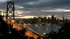 San Francisco's Oakland Bay Bridge grows brighter as darkness falls over the Stock Footage