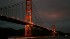 San Francisco's Golden Gate Bridge is illuminated in a darkening sky. Stock Footage