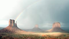 A rainbow fades in the sunlight following a storm over Monument Valley, Utah. - stock footage