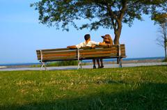 Stock Photo of Couple Relaxing On A Beach Bench