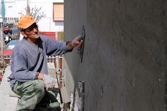 Man Plastering Wall - stock photo