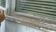 Stock Video Footage of home reno, scraping old paint off window frame, close up