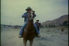 Stock Video Footage of Cowboys ride their horses fast across the desert in slow motion.