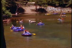 Kids ride innertubes on a river. Stock Footage