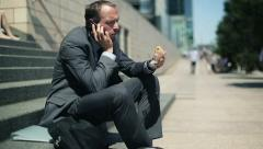 Businessman eating sandwich and talking on cellphone in the city HD Stock Footage