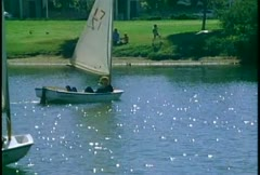 People leisurely float in sailboats on a small lake. Stock Footage