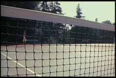 Two people play tennis as seen through the net. Stock Footage