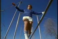 Stock Video Footage of A retro man walks on a tightrope in tennis shoes and shorts.