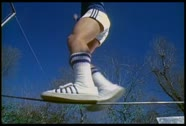 Stock Video Footage of A retro man walks on a tightrope in tennis shoes.