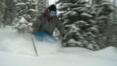 Advanced skier makes quick turns through powder in trees - stock footage