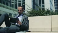 Businessman with tablet computer relaxing in the city HD Stock Footage