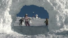 A young girl skier and older male snowboarder ride through snow arch - stock footage