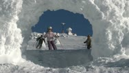A young girl skier and older male snowboarder ride through snow arch Stock Footage