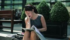 Businesswoman reading documents with bad news in city, steadicam shot HD Stock Footage