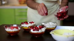 House wife decorating desserts with strawberries in the kitchen - stock footage