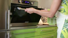 House wife remove freshly baked chocolate muffins from oven - stock footage
