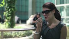 Beautiful businesswoman applying lip gloss in city, steadicam shot HD - stock footage