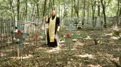 The Russian Orthodox Church. The priest is a prayer service at the cemetery. - stock footage